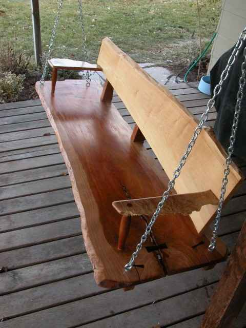 Custom porch swing made from cherry and maple logs. Wide slab swing.